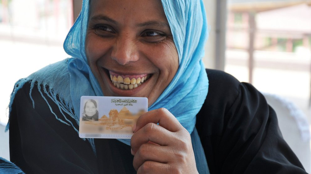 An Egyptian woman holds up her new national ID card